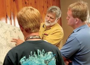 While Jordan Rose (left) of Windsor and Jody Sary (right) of Merry Hill look on, Brent Lane (background) of the First Colony Foundation points to a section of an old map that leads today's historians and archeologists to think that a portion of the famed Lost Colony may have relocated to the Merry Hill area of Bertie County. File Photo by Gene Motley