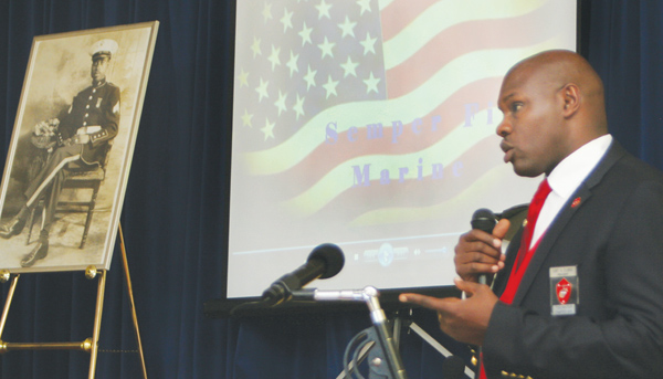A photo of Rev. Andrew Felton is displayed onstage (left) against a patriotic backdrop as retired US Marine Curt Clarke of the Montford Point Marine Association reads a tribute honoring Felton with the Congressional Gold Medal at the C.S. Brown Cultural Arts Center. Staff Photo by Gene Motley
