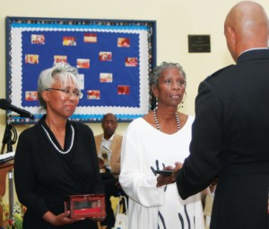 Michele (left) and Sharon Felton accept the Montford Point Marines Congressional Gold Medal and Certificate of Status for their late father, J. Andrew Felton, from Marine Lt. Col. Jason B. Davis. Staff Photo by Gene Motley