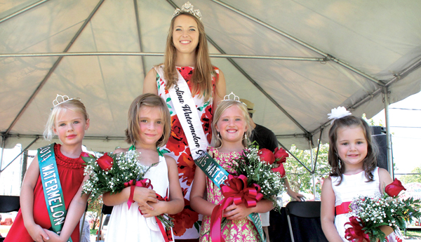 Maycee Lynn Hughes (second from right) was crowned as the 2015 NC Watermelon Festival Princess on Saturday during the annual competition held in Murfreesboro. She is the daughter of Wynne and Nichole Hughes of Edenton. Joslyn Taylor Flythe (second from left), the daughter of Daniel and Ashley Flythe of Conway, earned 1st runner-up honors, while Emma Rose Jones (right), the daughter of Abby Hoggard and Josh Jones of Conway, placed as 2nd runner-up. Carmen Honeycutt (background), the 2015 North Carolina Watermelon Queen, presided over the Little Princess contest, accompanied by the 2014 winner, Claire Flanagan (left). Staff Photo by Cal Bryant