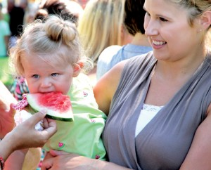 Austyn Rose Dunlow, daughter of Donnie and Terra Dunlow of Ahoskie, beats the heat by enjoying a cool slice of watermelon on Saturday morning just after the conclusion of the Watermelon Festival parade in downtown Murfreesboro. Staff Photo by Cal Bryant