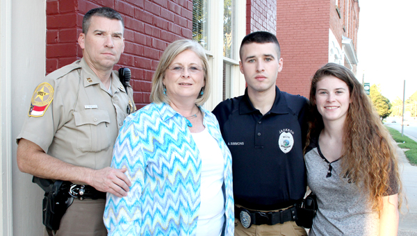 Jackson Police Officer Austin Simmons (second from right) is shown here with his parents, Brian and Lou Ann Simmons, and sister, Kelli (far right). The young officer was commended for his actions at the scene of a motor vehicle accident on July 20. Staff Photo by Cal Bryant