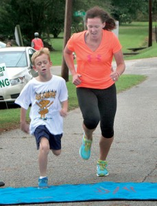 Mindy Drew (right) calls out encouragement to young Fin Terry from Kelford (left) as he crosses the finish line to win the Fun Run at the Aulander Peanut Festival on Saturday.  The rains did not dampen the activity for the adult runners 5K, or the kids who ran a shorter route. Staff Photo by Gene Motley