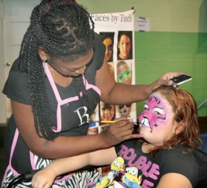 Trudi Vaughan of 'Faces by Trudi' paints a feline motif on the face of Brooke Taylor. Several dozen children – and adults – had their faces painted as part of the day's fun. Staff Photo by Gene Motley