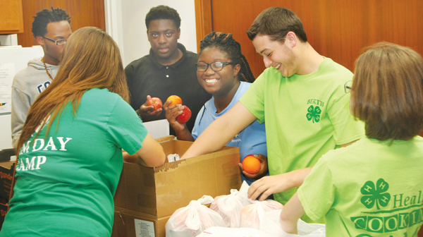 Bertie County 4-H Club members (from left) Tony Young, Abigail Castelloe (back to camera), Rakwon Watson, Sandrika Freeman, Aaron Belch, and Laura Belch share a laugh as they unload boxes of donated food for the Bertie Back-Pack Initiative. The food will be distributed to needy children for consumption on weekends. Staff Photo by Gene Motley