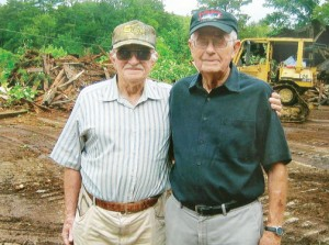 Percy Bunch (right) stands with John Glover in front of one piece of equipment clearing the way for the rebirth of Murfree Landing. Photo by Tim Flanagan