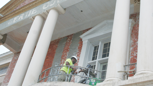 Sherwin Warren of SLW Consulting, supervising contractor for the Bertie County Courthouse renovation project, operates a dustless blaster on the structure's outer walls.  The old courthouse signage, visible from the blasting, is believed to have been painted during the 1920's. Staff Photo by Gene Motley