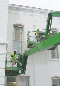 Local painters from Browning & Sons, A-Plus Painting, and Michael Bond Painting are supported by large boom lifts as they apply the new white paint coating to the Bertie County Courthouse.  Painting on the building is expected to continue throughout the fall. Staff Photo by Gene Motley