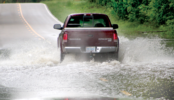 A pick-up truck throws up a small wake as it maneuvers through one of numerous locations in the Roanoke-Chowan area impacted by flooding associated with heavy rain that has fell across the region this week. Staff Photo by Cal Bryant