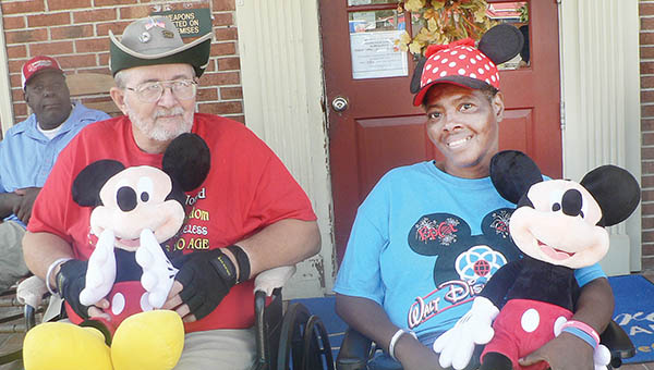 Photo by Kim Bunch Hoggard Creekside Health and Rehabilitation Center residents Herbert Yanke and Laverne Gatling pose with Mickey Mouse souvenirs from their recent trip to Disney World in Florida. | Photo by Kim Bunch Hoggard