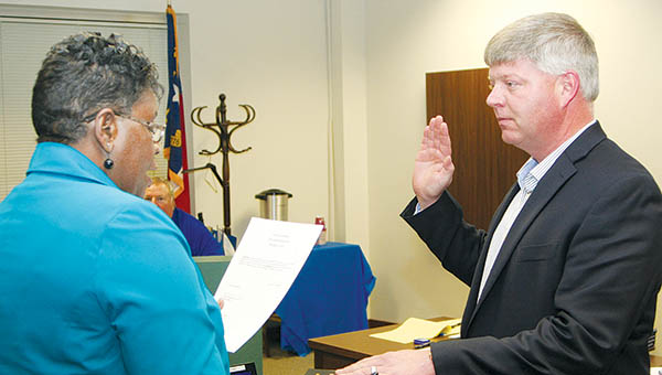 Bertie County Clerk of Superior Court Vasti James (left) administers the oath of office to County Tax Administrator Jodie Rhea (right) during the Nov. 2 meeting of the county's Board of Commissioners in Windsor.  Rhea will serve another term of four years.   Staff Photo by Gene Motley