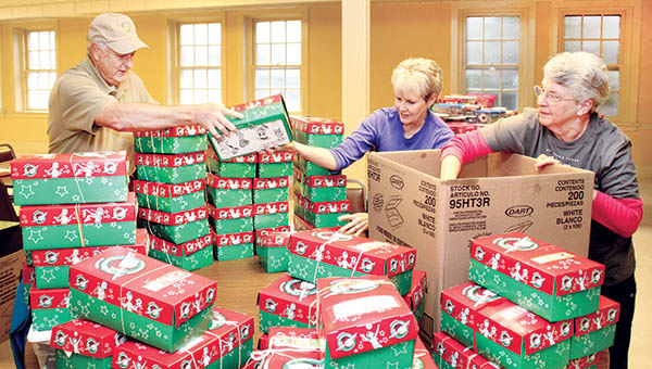 """Meherrin Baptist Church members A.B. Flanagan (left) and his wife, Ruth Anne (center), help Rosa Swain of First Baptist Church of Ahoskie sort through some of the """"shoebox"""" gifts that will soon find their way to less fortunate children around the world in time for Christmas. 