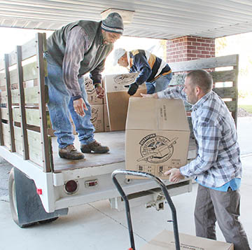 """Jason Perry (right) hands one of the Operation Christmas Child shipping boxes to Kenneth Holley while William Holley (background) carefully arranges another box on Monday morning. All totaled, 32 boxes (containing 558 """"shoebox gifts"""") were filled by the efforts of area churches."""