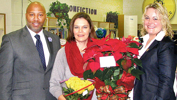 North Central Regional Teacher of the Year Marie Smith of Conway Middle School (center) is flanked by her principal, Oliver Holley, and 2015-16 North Carolina Teacher of the Year Keana Triplett during Wednesday's surprise announcement. | Photo by Keith Hoggard