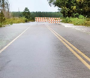 Water is shown rushing across Tyler Road near Rich Square in the aftermath of Tropical Storm Julia in late September. That road, impacted again by Hurricane Matthew in early October, remains closed and repairs are underway. | Photo by Angie Todd