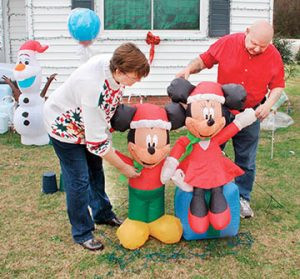 The couple is shown making last-minute adjustments to one of the many holiday decorations that line their front yard.