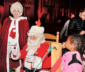 Dan and Bobbi Johnson also serve as Santa and Mrs. Claus at numerous local events during the Christmas season. Here they are shown waiting to hear from youngsters at last weekend's tree lighting ceremony in downtown Ahoskie. | Staff Photo by Gene Motley