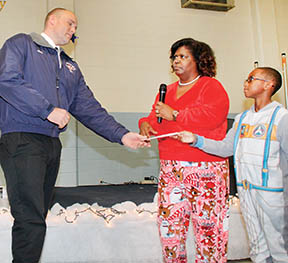 Woodland Fire Dept. Assistant Chief Chris Collier (left) accepts a check for $200 from 4th grader Evan Hoggard (right).