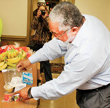 """RIGHT: Back Pack Initiative founder Ronald """"Ron"""" Wesson shows the nutritious foods contained in each back pack.  The packs are designed to fight hunger among students when they're away from school on weekends."""