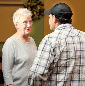 Barbara Outland, owner of the Grapevine Café in Woodland, greets national TV celebrity Dave Watson of The Outdoor Channel inside her restaurant on Friday night.