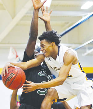Hertford County's Zion Riddick (in white) passes around a Northeastern defender in Tuesday night's game in Ahoskie.  The Bears beat the Eagles 75-73 in overtime for the second time this season and outright first-place in the conference. | Dynamic Photo / William Anthony