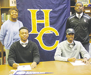 Hertford County High School had two football players commit in the school's Media Center on National Signing Day. (front, left) Defensive end Greg Harrell signed with CIAA member Elizabeth City State while wide receiver Jaquarii Roberson (front, right) inked a full scholarship with Wake Forest University of the ACC.  Also pictured are (back, left) HCHS principal Nora Artis and head football coach Terrance Saxby (back, right). | Staff Photo / Gene Motley
