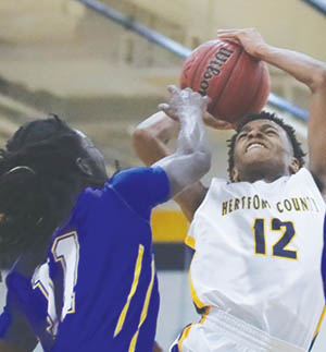Hertford County's Zion Riddick (#12) has his shot contested by Edenton's James Cofield in Saturday's Northeastern Coastal Conference game.  Riddick had 16 points as the Bears won their ninth league contest 68-62.   Dynamic Photo / William Anthony