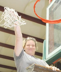 Ridgecroft School girls basketball coach Susan Oliver triumphantly holds aloft the nets after winning her latest Tarheel Independent Conference tournament championship.  The Lady Rams are now headed to the NCISAA state playoffs.