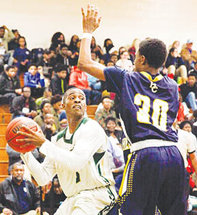 Hertford County's Talik Totten (in blue) guards Northeastern's Damar Sutton (left) in Friday night's Northeastern Coastal Conference Tournament boy's championship game.  After two overtime losses, Sutton and the Eagles finally topped the Bears, winning it 68-56.