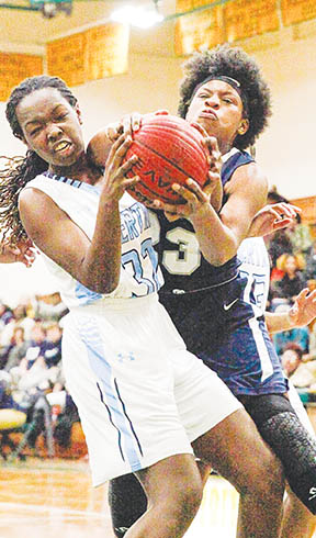 Bertie High's Carlisa Spivey (left) grapples for a rebound against Pasquotank's Kennedy Griffin in Friday night's Northeastern Coastal Conference Tournament girl's championship.  Spivey and the Lady Falcons won 57-38 and begin the state playoffs in Windsor tonight (Tuesday). | Keri Pampuch / The Daily Advance