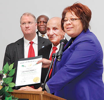 Eddie Buffaloe Sr. (foreground, center) was presented the prestigious Order of the Longleaf Pine by North Carolina General Assembly members – State Senator Erica Smith-Ingram and House Representative Michael Wray (left).