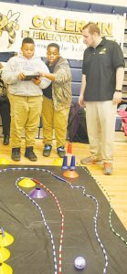 Colerain Elementary School science teacher Jeremy Peede (right) watches as students DeQuarius Ruffin (left) and Marquez Outlaw (middle) demonstrate movement of a robot-ball on an obstacle course by remote control with a tablet.